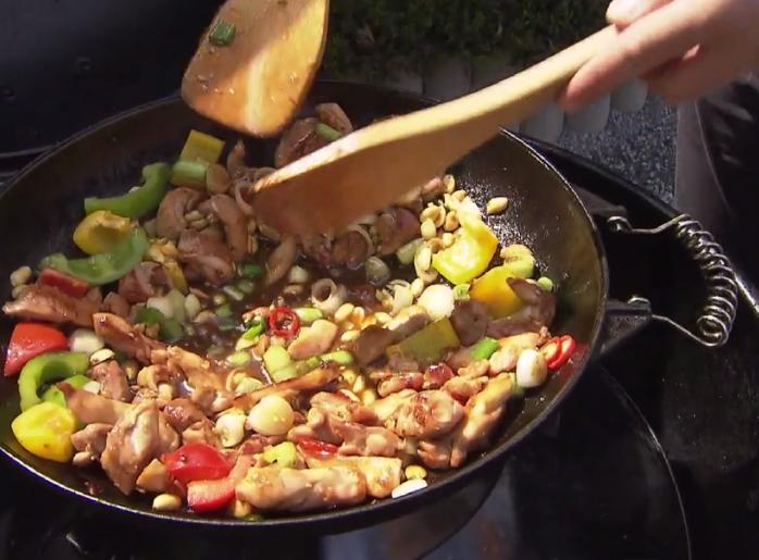 Pikantní karamelizované kuřecí kousky ve woku s arašídy, jarní cibulkou a koriandrem
